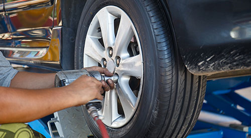 Tyre fitter unscrewing wheel nuts